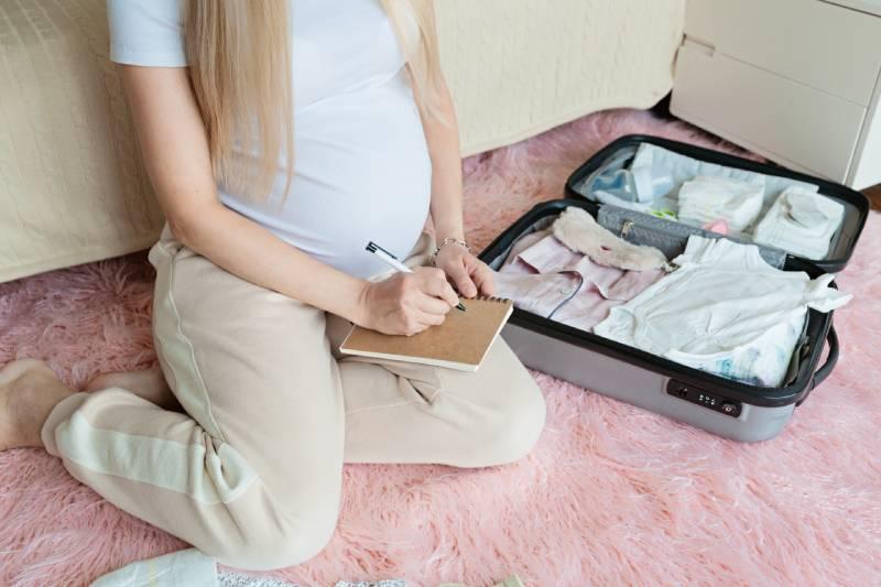 Schwangere bereitet Koffer für Geburt vor